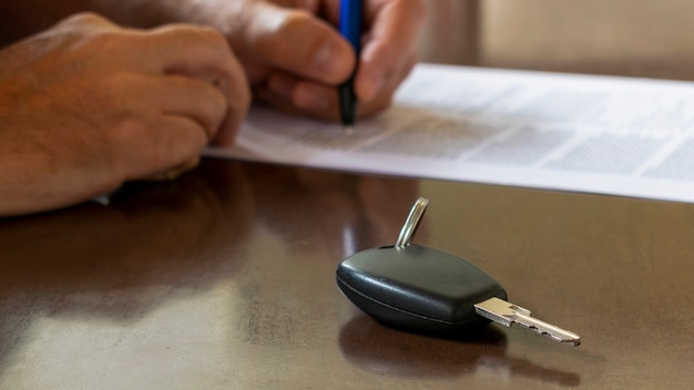 Detalhe da chave do carro e no fundo desfocado o homem assina contrato de carro para aluguel ou compra.