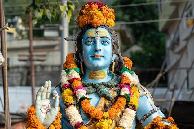 Detalhe da estátua de shiva, ídolo hindu no ghat perto do rio ganges em rishikesh, índia, close-up