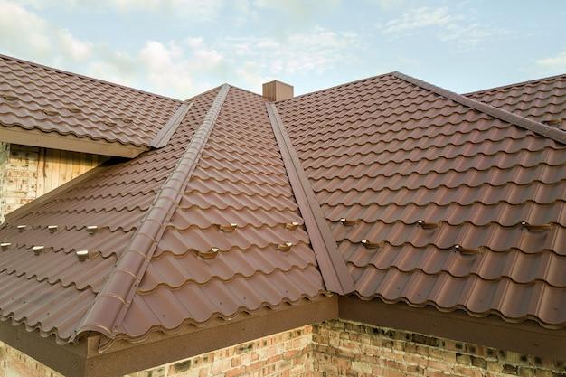 Detalhe da estrutura do telhado da casa coberto com telhas de metal marrom.