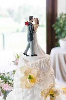 Detalhe da figura de um lindo casal recém-casado no topo de um lindo bolo de creme de casamento decorado com flores de fondant em uma mesa de festa de casamento