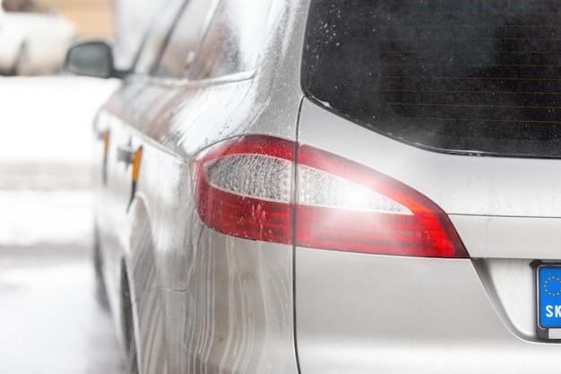 Detalhe da luz traseira de um carro moderno prateado dentro do lava-rápido com pingos de sabão