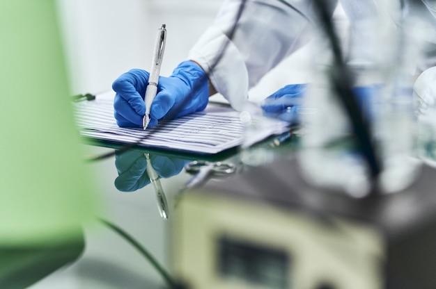 Detalhe da mão com luva de laboratório azul, anotando em uma folha de papel, cercada por gadgets de análise