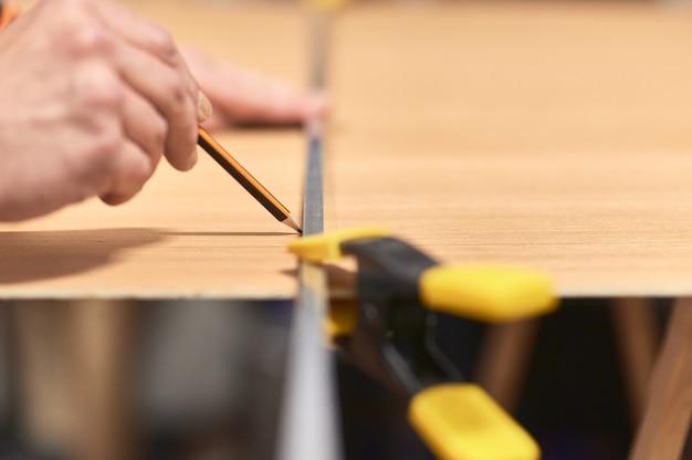 Detalhe da mão de um homem, fazendo uma marca com um lápis e um guia de metal em uma placa de madeira. o guia é mantido no lugar com um grampo.