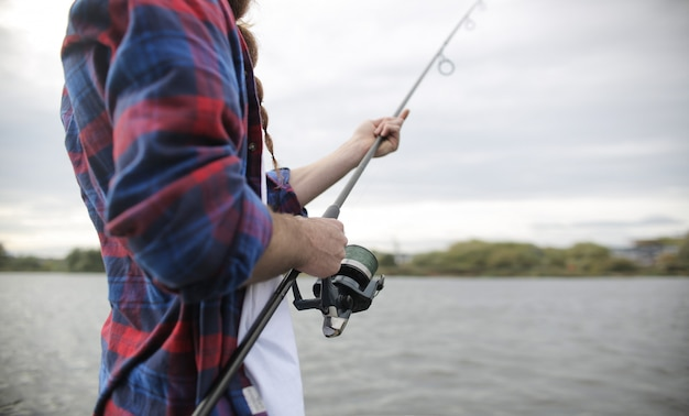 Detalhe da mão de um homem na vara de pescar