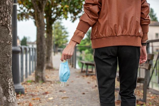 Detalhe da mão de uma garota segurando uma máscara médica enquanto caminhava na rua durante uma quarentena cobiçada