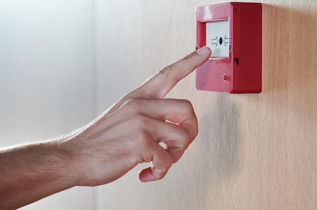 Detalhe da mão do homem prestes a apertar um botão de emergência