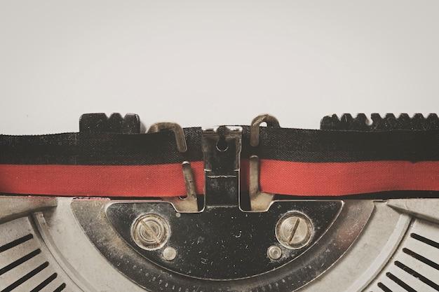 Detalhe da máquina de escrever vintage com folha de papel branco
