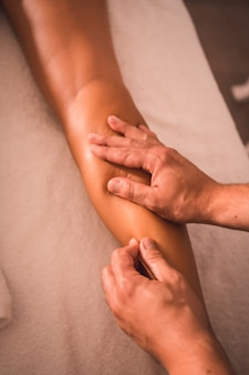 Detalhe da massagem de um fisioterapeuta nas costas da perna direita de uma jovem deitada sobre a mesa. fisioterapia, osteopatia, massagem relaxante, movimento vídeo de tratamento nas costas