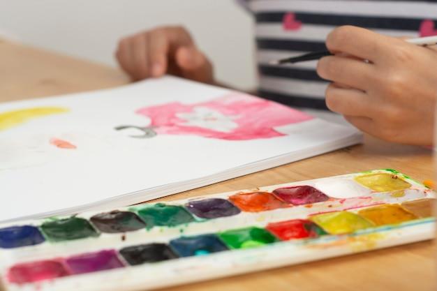Detalhe da pintura da mão da criança com aquarela, passatempo, educação.
