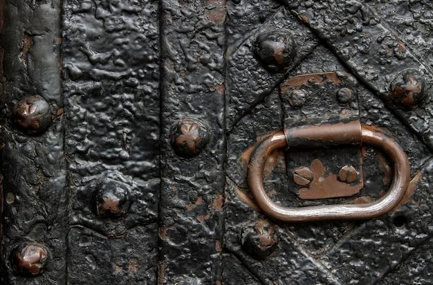 Detalhe da porta de ferro forjado com uma alça de metal. placas encadernadas e unhas velhas encaracoladas