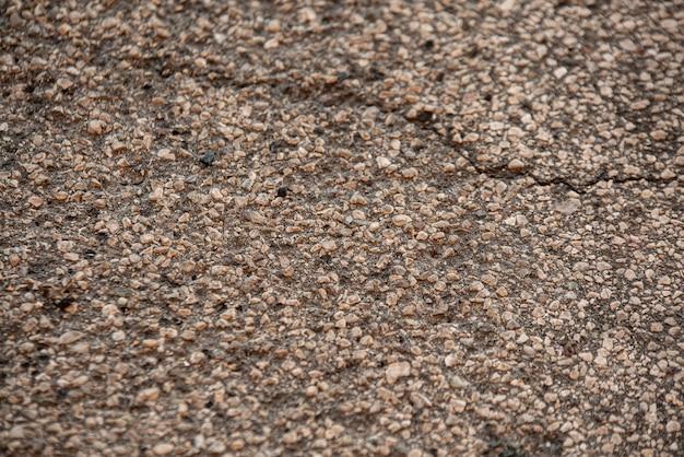 Detalhe da textura do asfalto com rachaduras e marco de tiro
