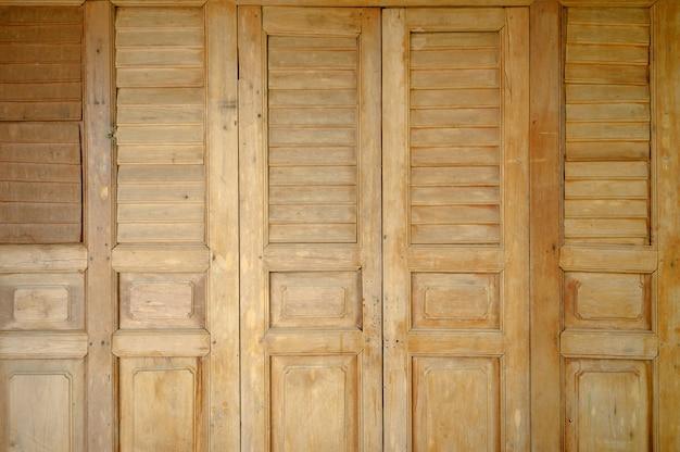 Detalhe da textura do fundo de estilo tailandês de madeira da porta natural velha.