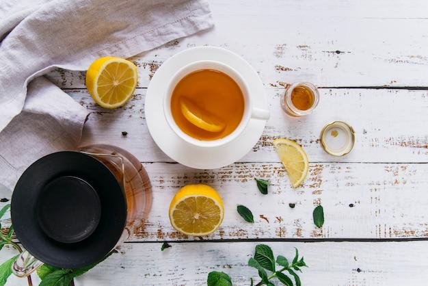 Detalhe da xícara de chá com limão e hortelã fresca na mesa de madeira branca