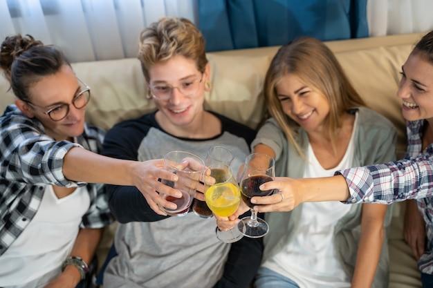 Detalhe das mãos de um grupo de jovens com óculos brindando