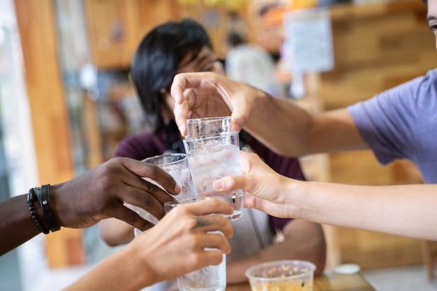 Detalhe das mãos de um grupo de jovens de diferentes etnias brindando com óculos em um restaurante