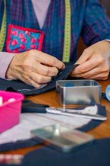 Detalhe das mãos de uma costureira sênior, costurando um pano para fazer uma peça de roupa em sua oficina