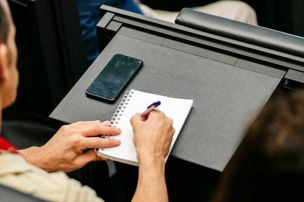 Detalhe das mãos de uma mulher escrevendo em um caderno em um congresso