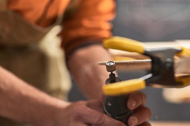 Detalhe das mãos do carpinteiro, arquivando a borda de uma prancha de madeira com uma ferramenta dremel. há um grampo fora de foco, segurando tudo em primeiro plano.