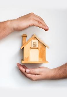 Detalhe das mãos masculinas em torno de uma pequena casa de madeira