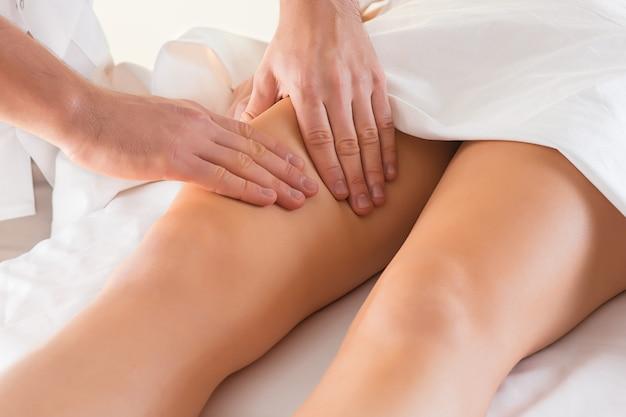 Detalhe das mãos massageando o músculo da panturrilha humana.