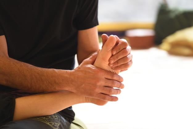 Detalhe das mãos massageando o pé do seu parceiro.