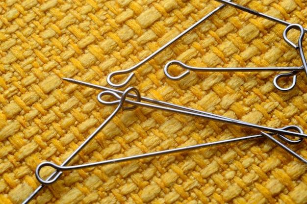 Detalhe de alfinetes de costura amarelos em fundo de textura amarela.
