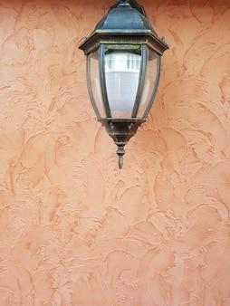 Detalhe de alta resolução de parede de concreto laranja com latern pendurado