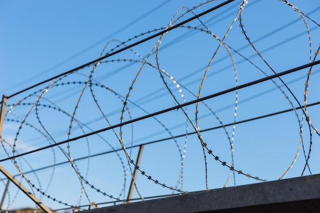 Detalhe de arame farpado em cima da cerca de segurança com céu azul ao fundo