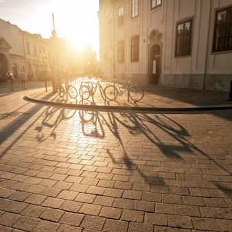 Detalhe de bicicletas estacionadas com sombras na calçada
