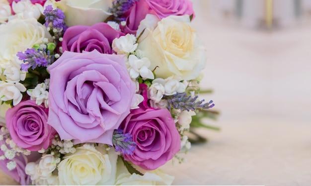 Detalhe de buquê de rosas roxas e brancas com espaço para escrever