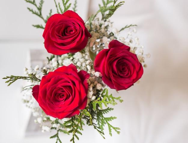 Detalhe de buquê de rosas vermelhas com fundo branco e espaço para escrever