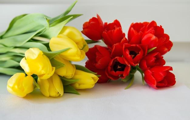Detalhe de buquê de tulipas vermelhas e amarelas com fundo branco