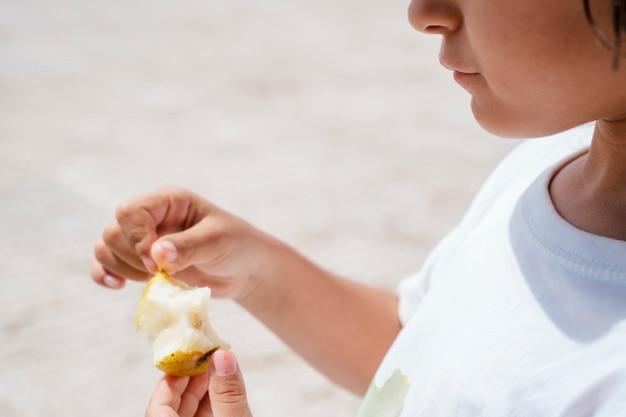 Detalhe de criança pequena irreconhecível que come a pera fresca ao ar livre. estilo de vida de férias de verão com crianças. nutrição saudável para equilibrar a dieta em crianças. coma frutas todos os dias para uma boa saúde.