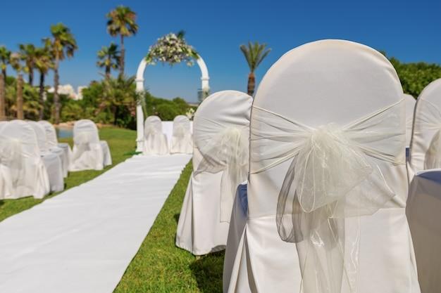 Detalhe de decoração da cadeira de arco para a cerimônia de casamento no jardim. fechar-se.