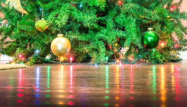 Detalhe de enfeites de árvore de natal com reflexos de luzes no chão