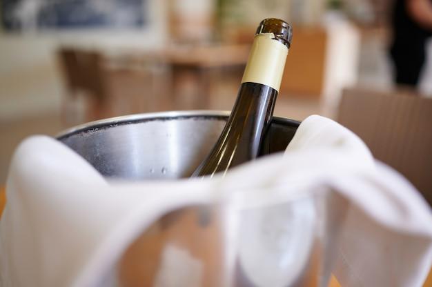 Detalhe de garrafa de vinho em um balde de gelo com foco seletivo