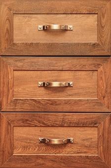 Detalhe de gavetas de móveis decorados. gaveta velha - amortecedor. detalhe de close-up de armários de madeira de carvalho de alta qualidade com puxadores de gaveta de bronze