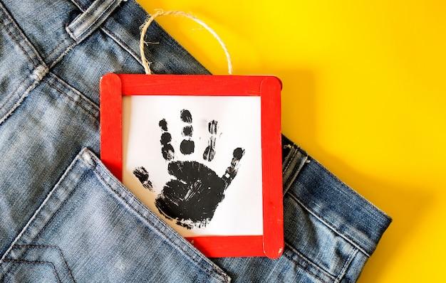 Detalhe de jeans homem com moldura artesanal com uma mão de criança estampada no bolso