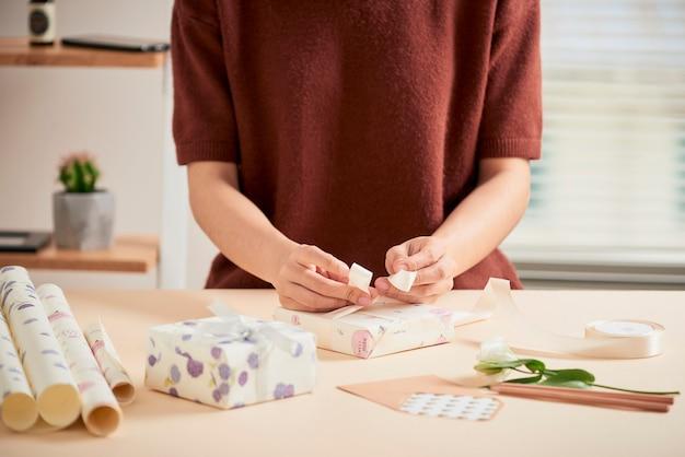 Detalhe de mãos de mulher embalando presentes com papel de presente