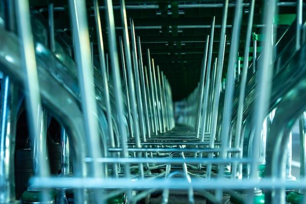 Detalhe de muitos troles verdes e plásticos do supermercado empilhados na entrada de uma loja.