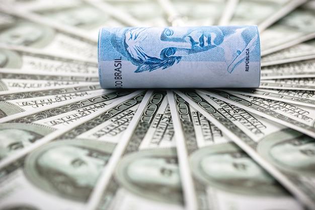 Detalhe de nota de cem reais cercada por notas de 100 dólares, conceito de crise financeira entre brasil e estados unidos