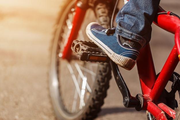 Detalhe de pés do ciclista da criança que montam a bicicleta em exterior na estrada ensolarada. closeup no pedal e pé