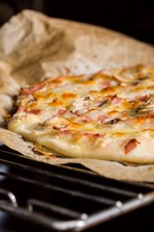 Detalhe de pizza caseira na grelha do forno