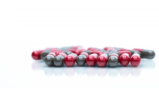 Detalhe de tiro macro de comprimidos cápsula vermelhos e cinza isolados