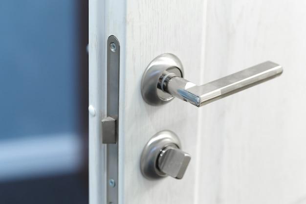 Detalhe de um botão metálico na porta branca horizontal