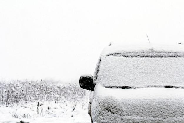 Detalhe de um carro na rua durante a queda de neve no inverno
