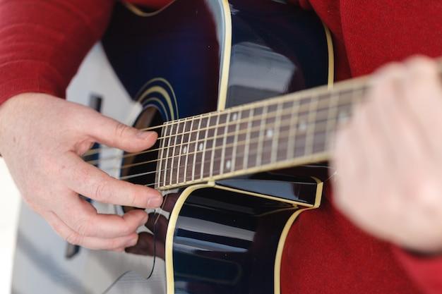 Detalhe de um guitarrista tocando uma guitarra clássica