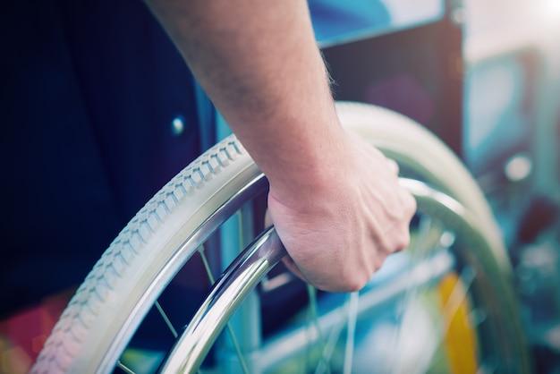 Detalhe de um homem com deficiência em cadeira de rodas