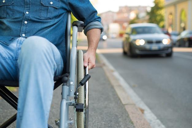 Detalhe de um homem usando uma cadeira de rodas em uma rua urbana