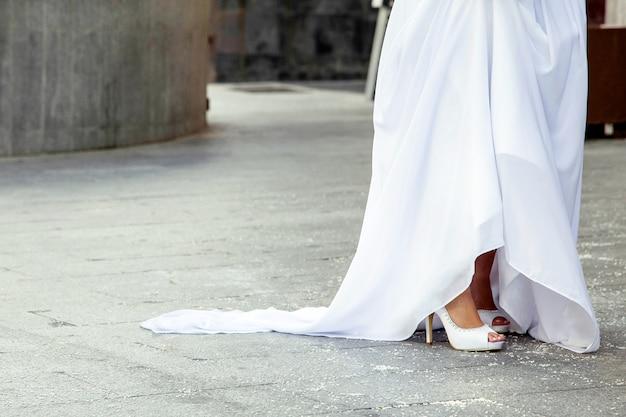 Detalhe de um lindo vestido de noiva e sapatos em um dia de casamento e arroz no chão